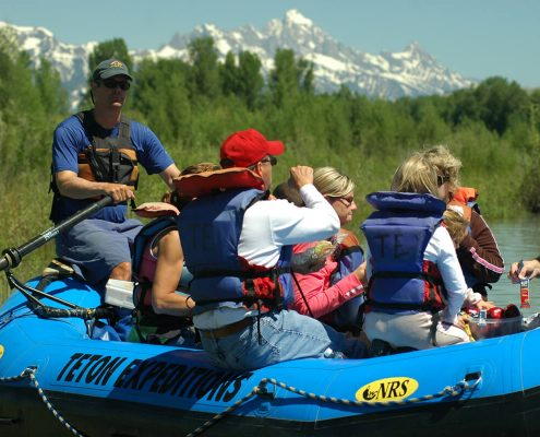 six people on a blue raft wearing life preservers on a river