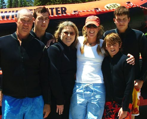 family of six smiling and posing for picture after river float trip