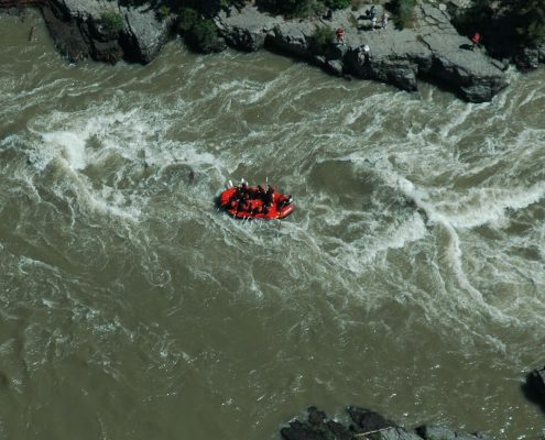 distant view of red raft on small river rapids