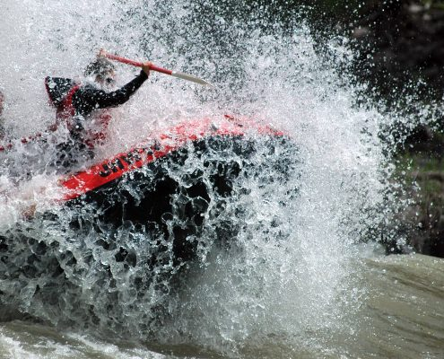 person on red raft paddling through rapids on river