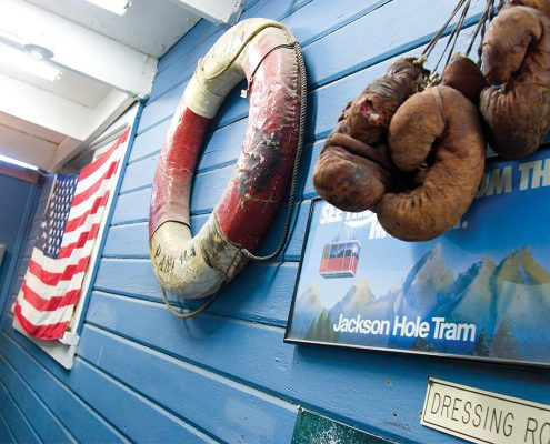 blue wood wall with American flag, life ring, and old boxing gloves hung on it