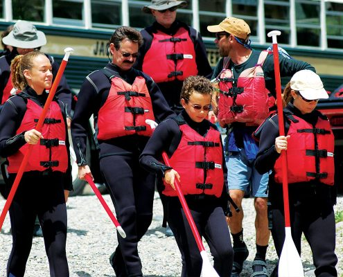 group of people wearing red life vests walking with raft paddles