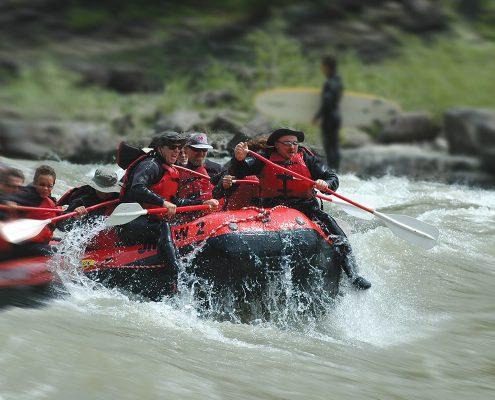 group of people paddling through rapids in raft