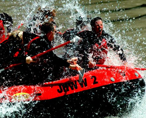 group of people being splashed with water going through river rapids