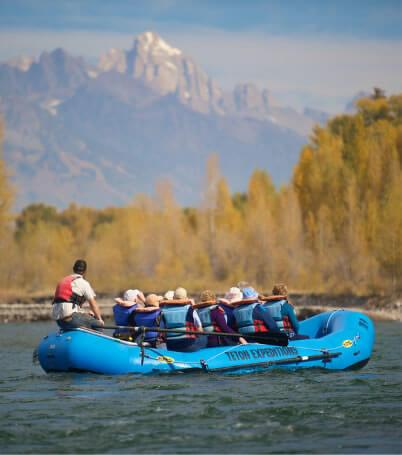 group of people in blue raft taking scenic float trip on river
