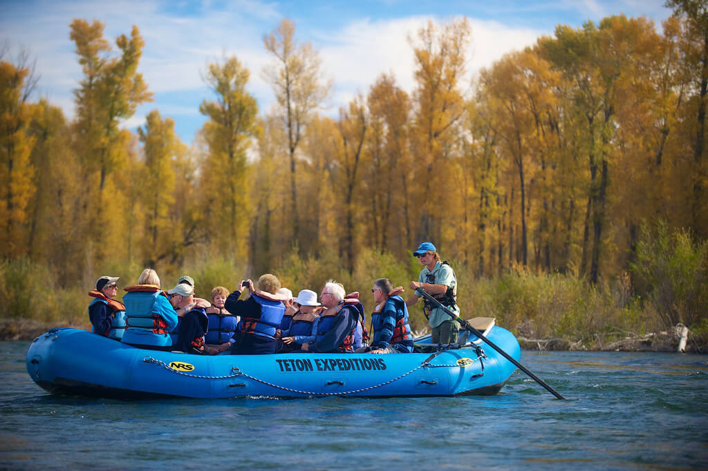 group of people in blue raft taking scenic float trip on river with yellow trees in background