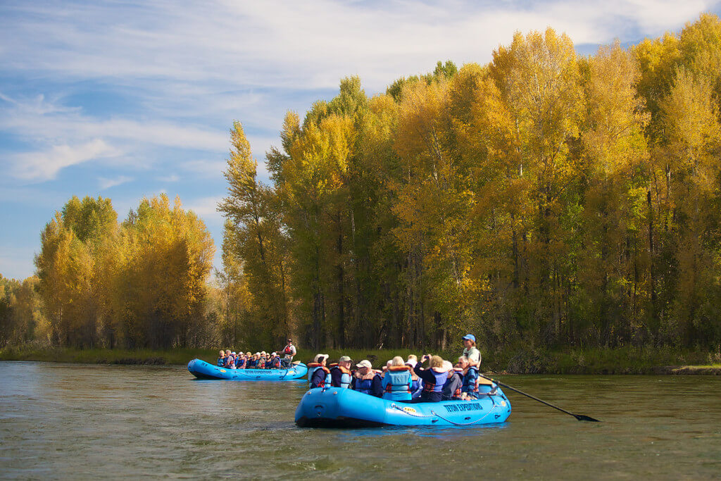 two groups of people in rafts on river