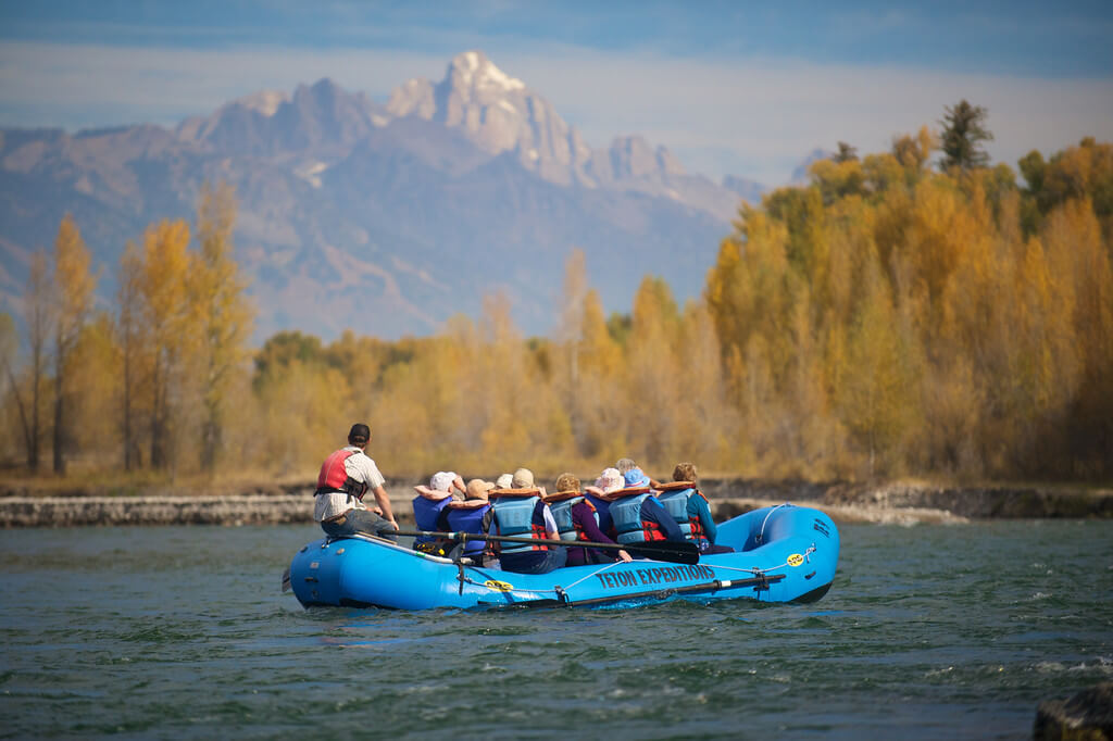 group of people in raft with mountains in the background