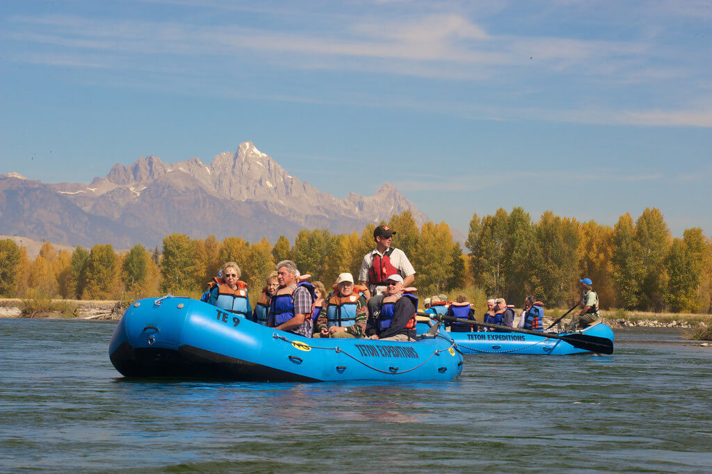 two groups of people in rafts on river with mountains in background