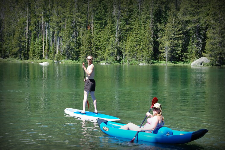 man on standup paddle board and woman in single canoe on river