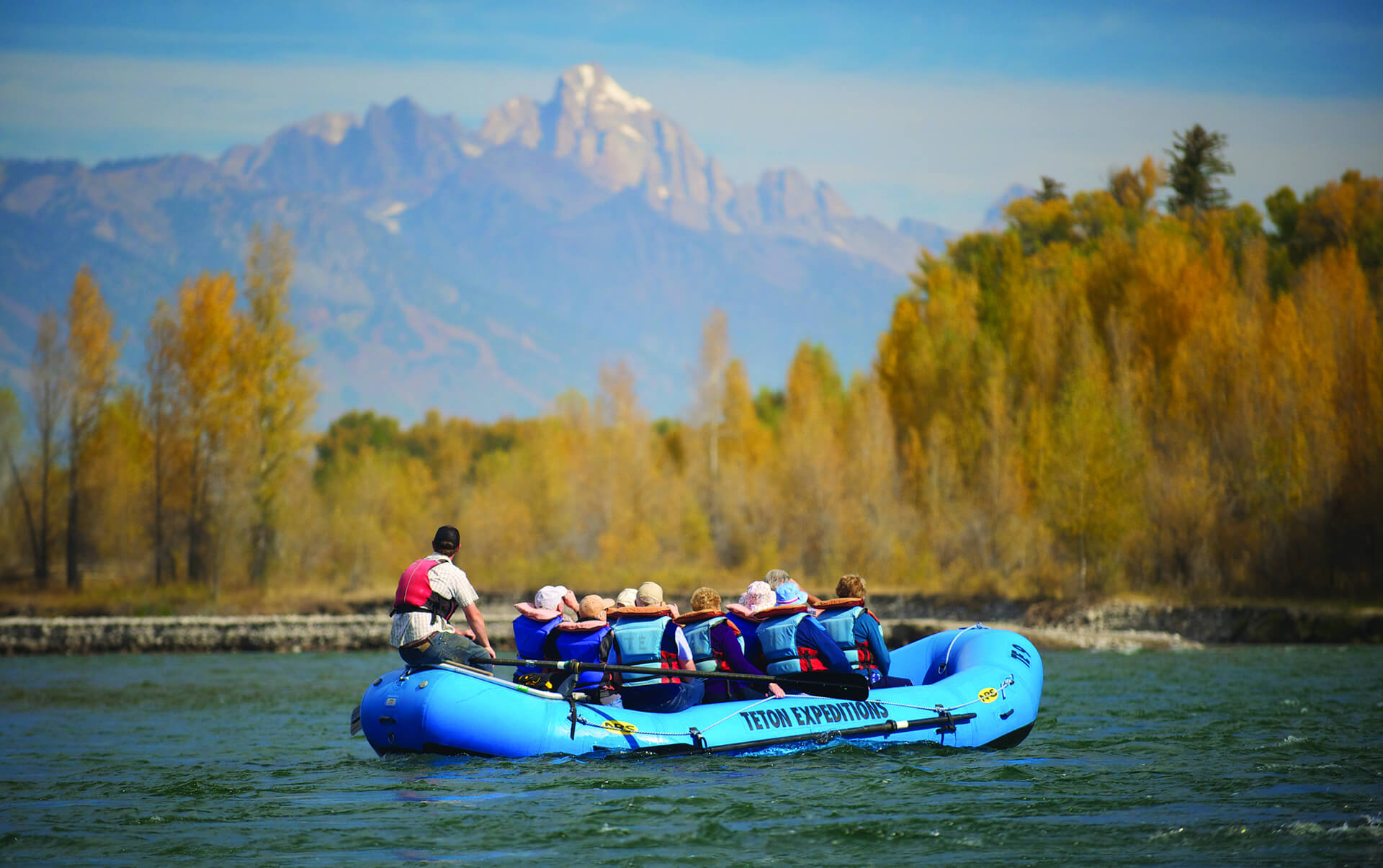 group of people on scenic float trip with mountains in background